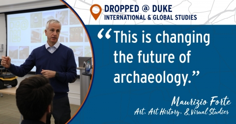 """Prof. Maurizio Forte standing in front of a screen -- """"This is changing the future of archaeology"""""""