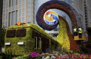 Workers on a platform install flowers on a decoration in a shape of a train for promoting the Belt and Road Forum in Beijing, April 23, 2019. Image Credit- AP Photo Andy Wong.jpg